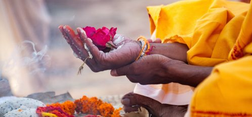 Woman holding flowers in her hand at a Hindu worship service.