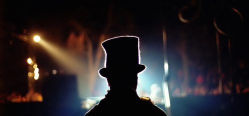 Performer with a hat on stannding on a dark stage facing silhouette of audience members.
