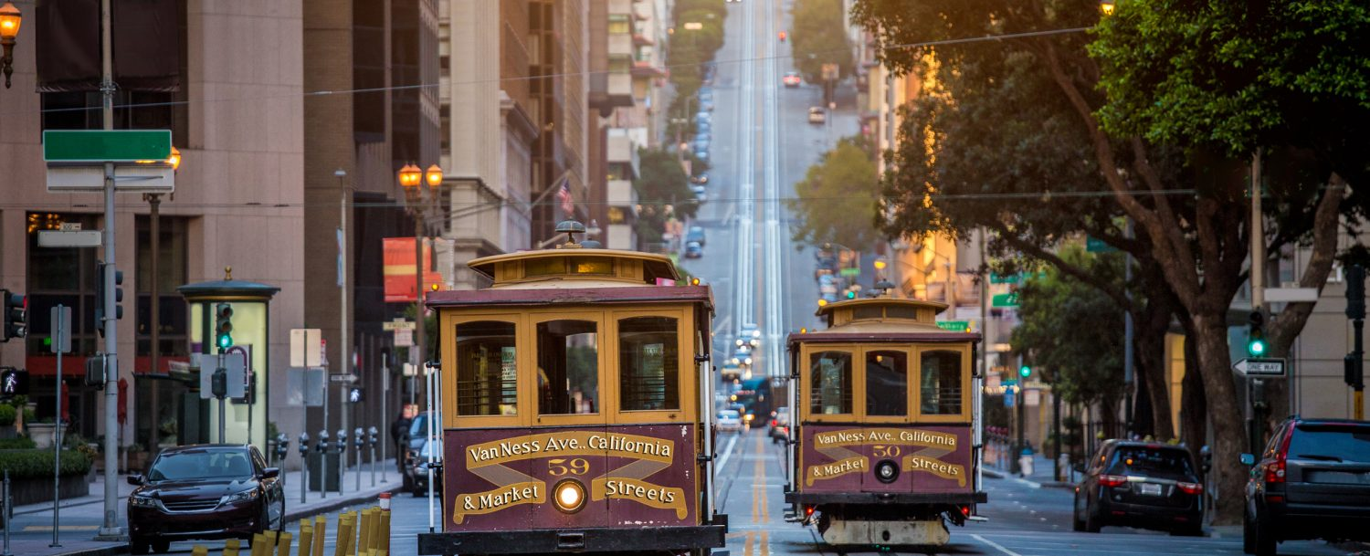 Classic view of historic traditional Cable Cars riding on famous California Street in beautiful early morning light at sunrise in summer, San Francisco, California, USA.