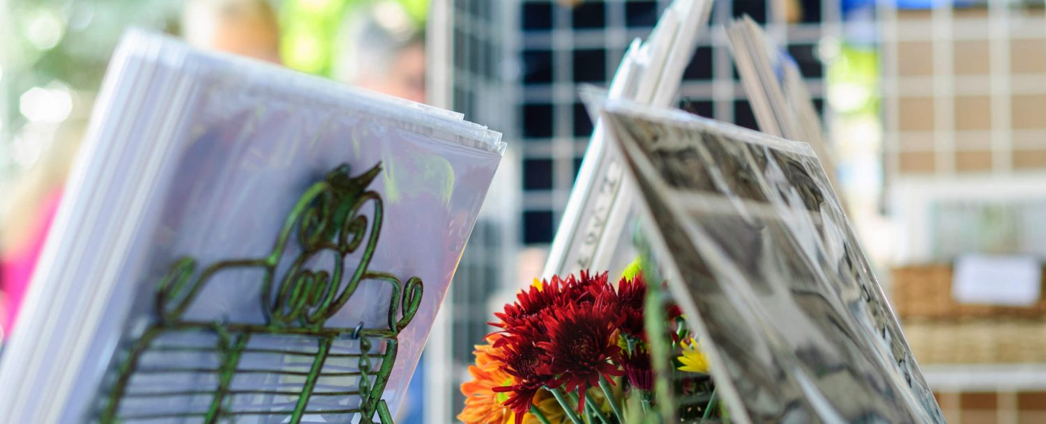 A display of photographs and flowers in a vase at the Livermore Artwalk.