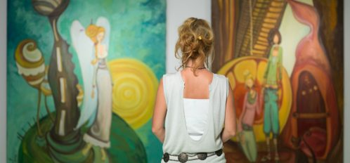 A woman standing in an a studio viewing two pieces of artwork on the wall at SF Open Studios.