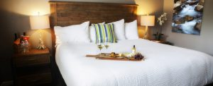 A king bed with wine and a cheese platter in the Olive Hill King Room at the Purple Orchid Resort & Spa.