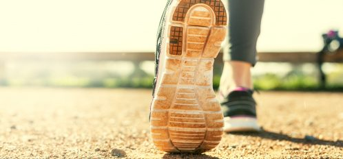 Woman running with close up of her runnning shoes.