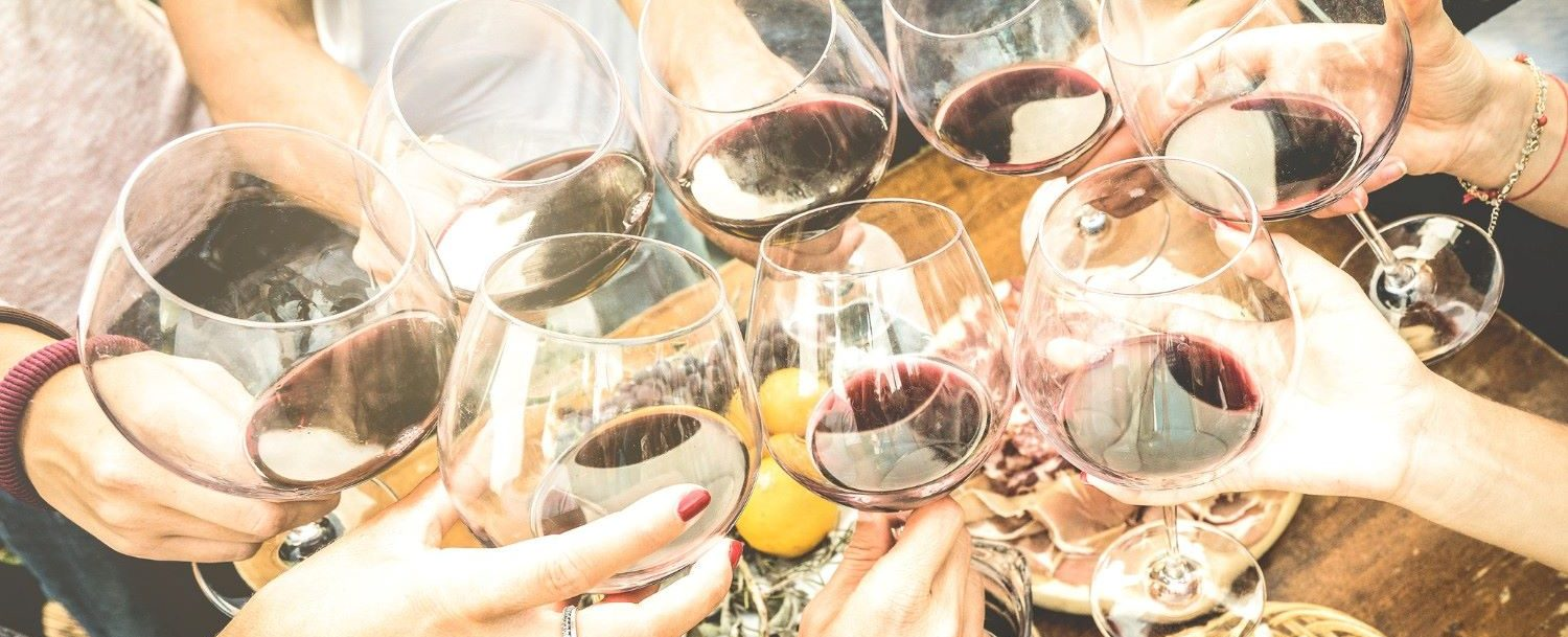 People toasting glasses of red wine at a tasting.