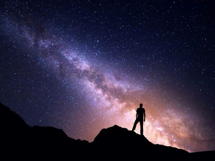 Person standing atop a summit stargazing.