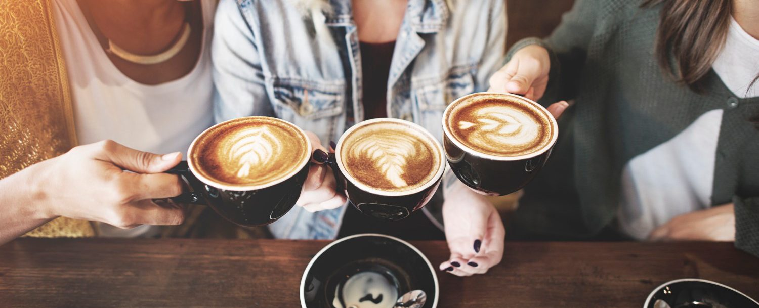 Three women chatting and holding coffee cups.