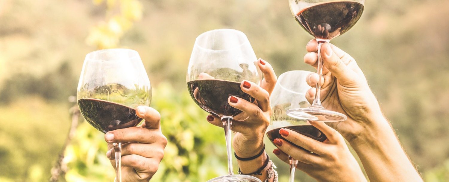 Four women raising a toast with red wine.