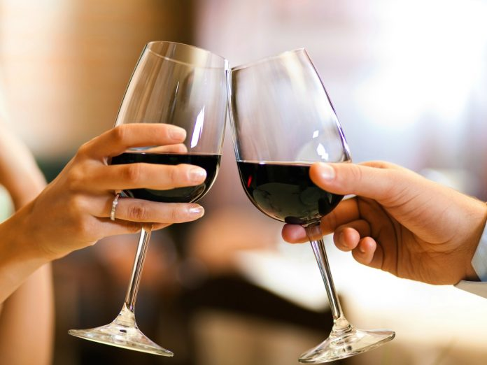 Woman and man raising a toast of glasses with red wine.