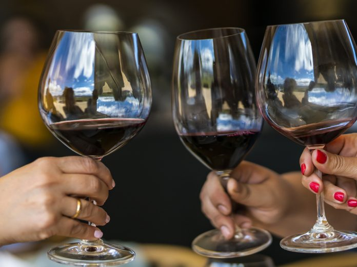 Three women holding red wine glasses and toasting