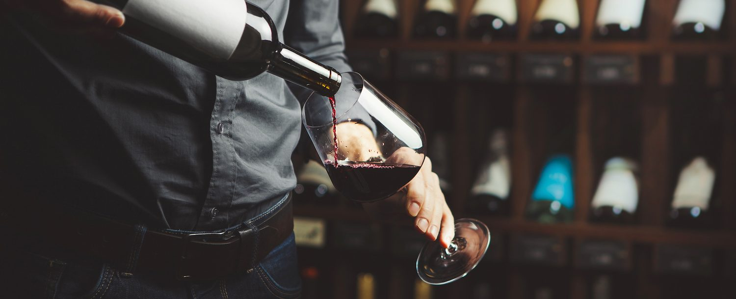 Man pouring red wine into a glass for a wine tasting.